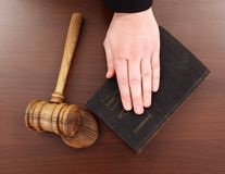 Hand on law book and gavel. Hand resting on law book, wooden justice gavel beside royalty free stock image