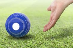 Hand And Lawn Bowl. A male hand bowling and releasing a blue wooden lawn bowling ball on a green lawn grass surface -3D render Stock Photos