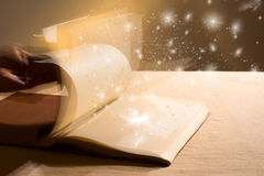 Hand leafing through a book with blank pages magic light. Stock Images