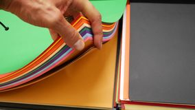 Hand leafing through thick colored paper sheets stock footage