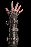 Hand in Leather Cuffs on Black. Hand in Leather Cuffs Royalty Free Stock Photography