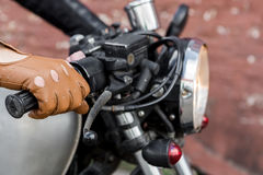 Hand in leather glove hold throttle control. Close up of a hipster biker man hand in leather glove hold throttle control of classic style cafe racer motorcycle Stock Image