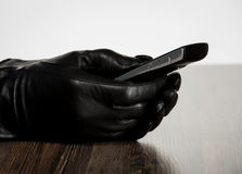 Hand in leather glove holding cellphone Royalty Free Stock Image
