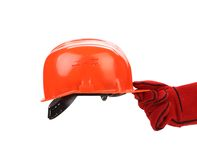 Hand in leather gloves holds hard hat. Royalty Free Stock Photo