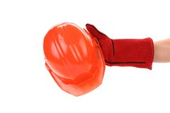 Hand in leather gloves holds hard hat. Stock Image