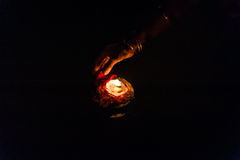 Hand leaving a burning candle during the aarti Stock Images