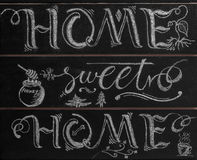 Hand lettering calligraphy sign drawn with chalk. Lettered quote. `Home sweet home Royalty Free Stock Image