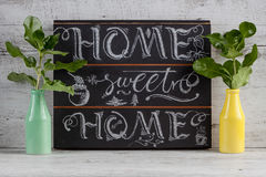 Hand lettering calligraphy sign drawn with chalk. Lettered quote. `Home sweet home` to use as decoration or in greeting cards Royalty Free Stock Image