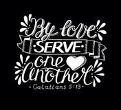Hand lettering with bible verse By love serve one another made on black background. Hand lettering By love serve one another. Biblical background. Christian Stock Images