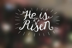 Hand lettering He is risen with a cross. Stock Image