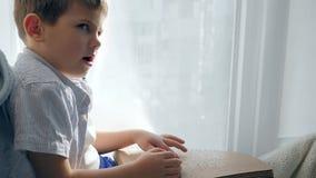 Hand-lezing van blind kind met braille-boekzitting op vensterbank stock videobeelden