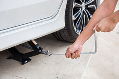 Hand lifting a car with spanner jack royalty free stock image
