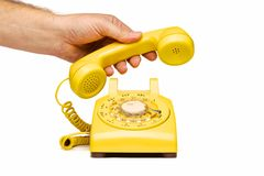 Hand lifting hand piece of yellow phone Royalty Free Stock Images