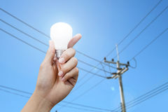 Hand with light bulb, electricity pole background Stock Photos