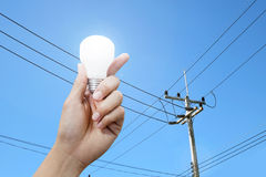 Hand with light bulb, electricity pole background Stock Photography