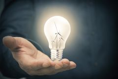 Concept of renewable energies. Hand with light bulb and windmills, concept of renewable energies stock photography