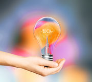 Hand with light bulb and the word idea Stock Photo
