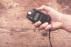 Hand with light meter. A hand is holding a light meter against wood background Stock Photography
