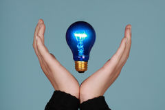 Hand and lightbulb Stock Photos