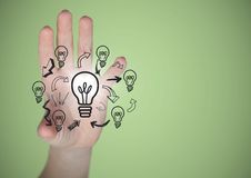 Hand with lightbulb doodles and flare against green background Royalty Free Stock Images
