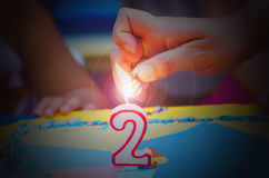 Hand with a lighter about to fire a two years birthday candle.jp Royalty Free Stock Photo