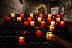 Hand lighting a candle in the church. stock photography