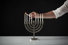 Hand Lighting Candle On Metal Hanukkah Menorah On Marble Surface Against Black Studio Background royalty free stock photography