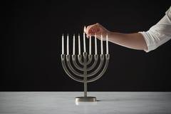 Hand Lighting Candle On Metal Hanukkah Menorah On Marble Surface Against Black Studio Background royalty free stock photo