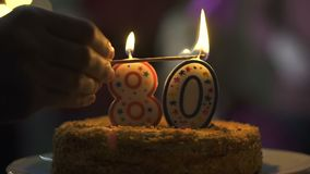 Hand lighting candles birthday cake, 80 anniversary celebration, tasty dessert. Stock footage stock video