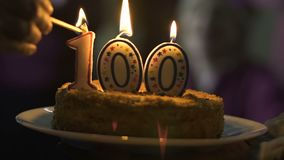Hand lighting candles 100 on cake, company anniversary celebration, ceremony. Stock footage stock video