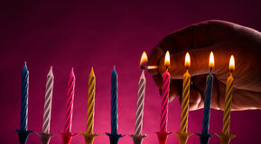 Hand lighting up birthday candles. Man's hand lighting up with a burning match ten colorful birthday candles over bright purple background Royalty Free Stock Images