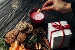 Hand lighting up candle and present gingerbread cookies garnet o Royalty Free Stock Photography