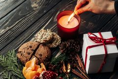 Hand lighting up candle and present gingerbread cookies garnet o Royalty Free Stock Image