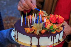 Hand lights candles on the birthday cake royalty free stock photos