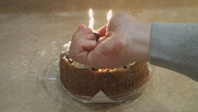 Hand lights the candles on the cake stock video