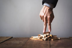 Hand liken business person stepping up a toy wooden block to goa Stock Photography