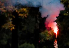 Red smoke bomb in a hand royalty free stock photo