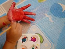Hand of a little baby being painted with red color - baby handprint / fingerprint painting. Hand of a little baby being painted with red color - baby`s handprint stock photo