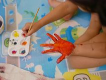Hand of a little baby being painted with red and orange colors - baby handprint / fingerprint painting. Hand of a little baby girl being painted with red and royalty free stock photo