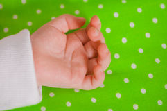 Hand of a little baby sleeping on a  cushion. Hand of a little baby sleeping on a green cushion Royalty Free Stock Photo