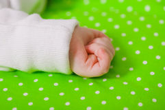 Hand of a little baby sleeping on a  cushion. Hand of a little baby sleeping on a green cushion Royalty Free Stock Photos