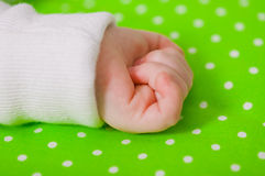Hand of a little baby sleeping on a  cushion. Hand of a little baby sleeping on a green cushion Royalty Free Stock Images