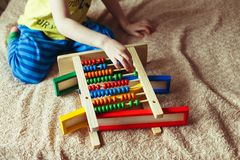 Hand of little boy playing with abacus. Clouse up picture of curly cute toddler playing with wooden toy. Children education royalty free stock photo