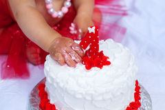 Hand of little child destroys birthday cake. Closeup Stock Photography