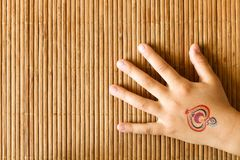 Hand of little girl with baby tattoo on bamboo background. Hand of little girl with baby tattoo on bamboo background royalty free stock image
