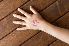 Hand of little girl with baby tattoo on wooden background. Hand of little girl with baby tattoo on wooden background stock photos