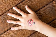 Hand of little girl with baby tattoo on wooden background. Hand of little girl with baby tattoo on wooden background royalty free stock images