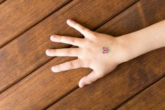 Hand of little girl with baby tattoo on wooden background. Hand of little girl with baby tattoo on wooden background royalty free stock image