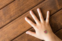 Hand of little girl with baby tattoo on wooden background. Hand of little girl with baby tattoo on wooden background royalty free stock photo