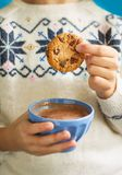 Hand of little girl dunking cookie in hot chocolate milk. Close up Royalty Free Stock Photo